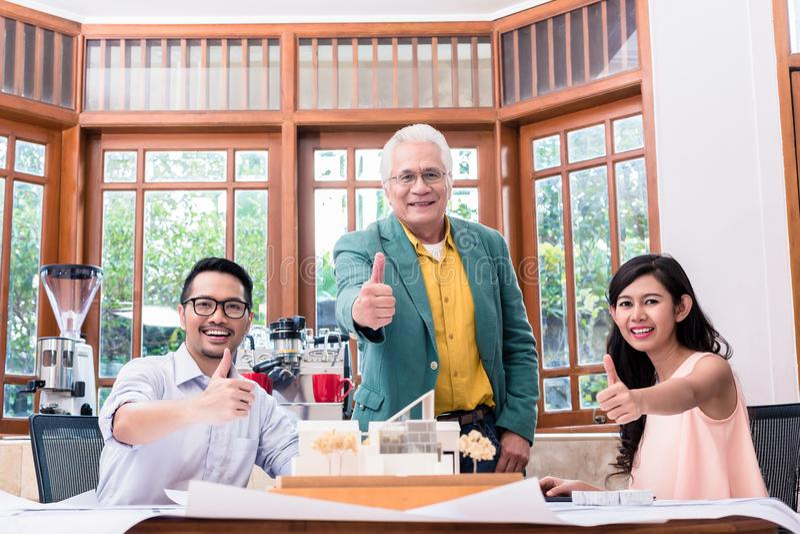 Equipe de três arquitetos bem sucedidos que mostram os polegares acima imagens de stock royalty free