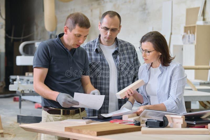 A equipe de trabalhadores da oficina do woodworking está discutindo O cliente, o desenhista ou o coordenador e os trabalhadores d imagem de stock royalty free