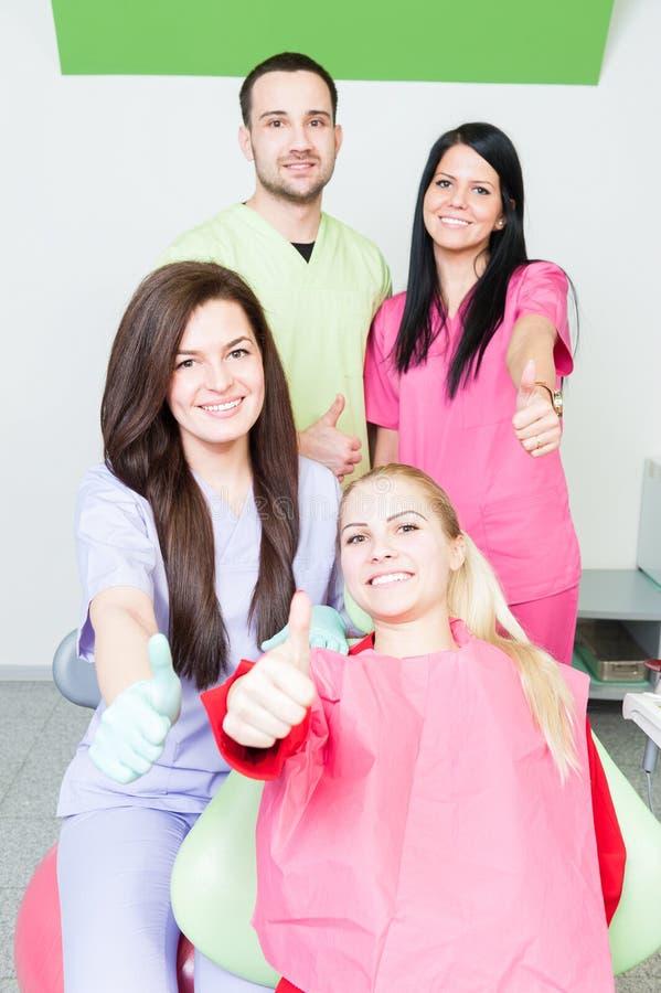 Equipe dental bem sucedida que mostra como o gesto fotos de stock