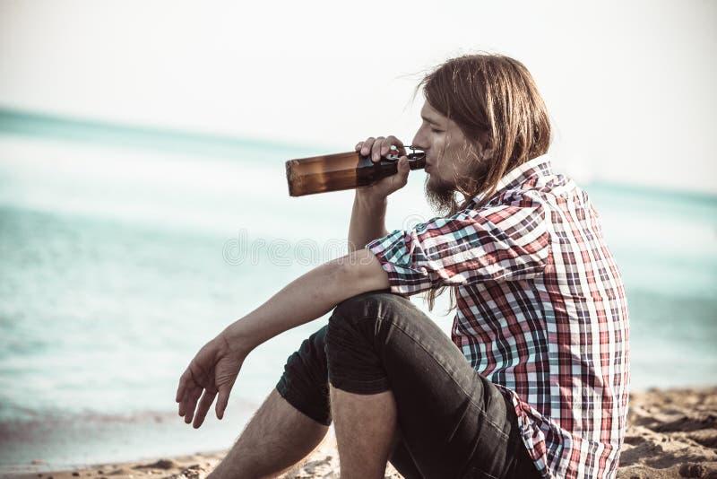 Equipe deprimido com a garrafa de vinho que senta-se na praia exterior fotografia de stock royalty free