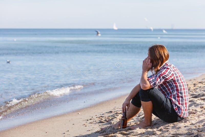 Equipe deprimido com a garrafa de vinho que senta-se na praia exterior foto de stock royalty free