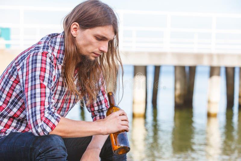 Equipe deprimido com a garrafa de vinho que senta-se na praia exterior fotos de stock royalty free