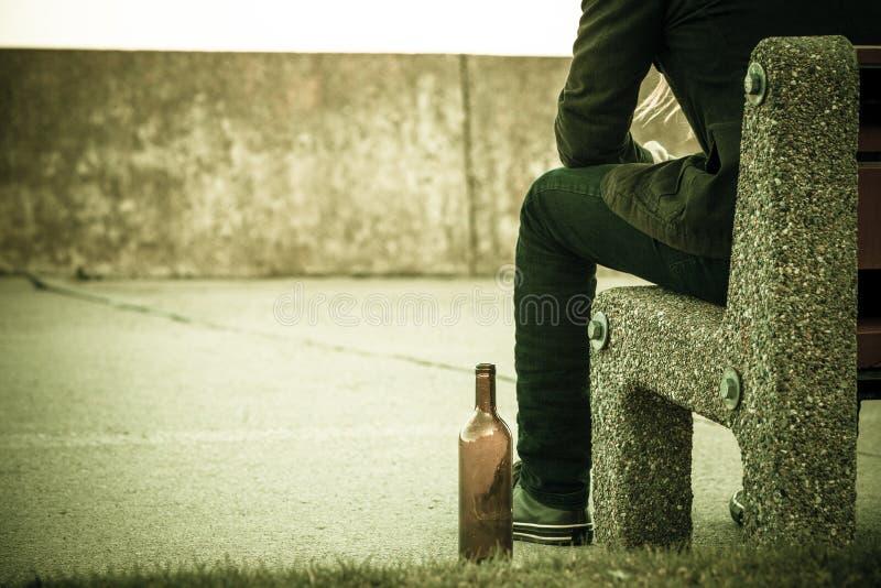 Equipe deprimido com a garrafa de vinho que senta-se no banco exterior imagem de stock