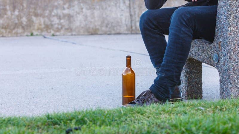 Equipe deprimido com a garrafa de vinho que senta-se no banco exterior fotografia de stock