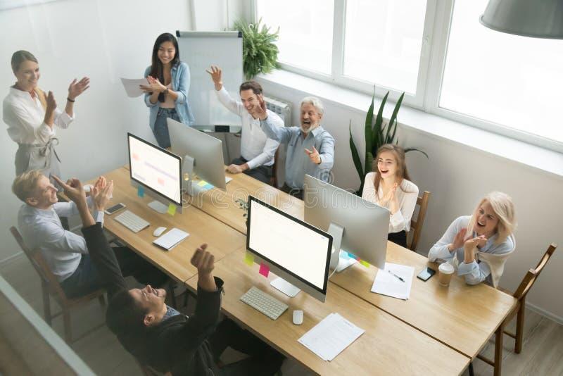 A equipe diversa entusiasmado que felicita o colega preto com consegue imagens de stock royalty free