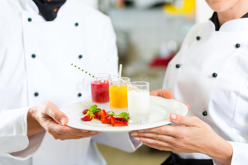 Equipe do cozinheiro chefe na cozinha do restaurante com sobremesa imagem de stock royalty free