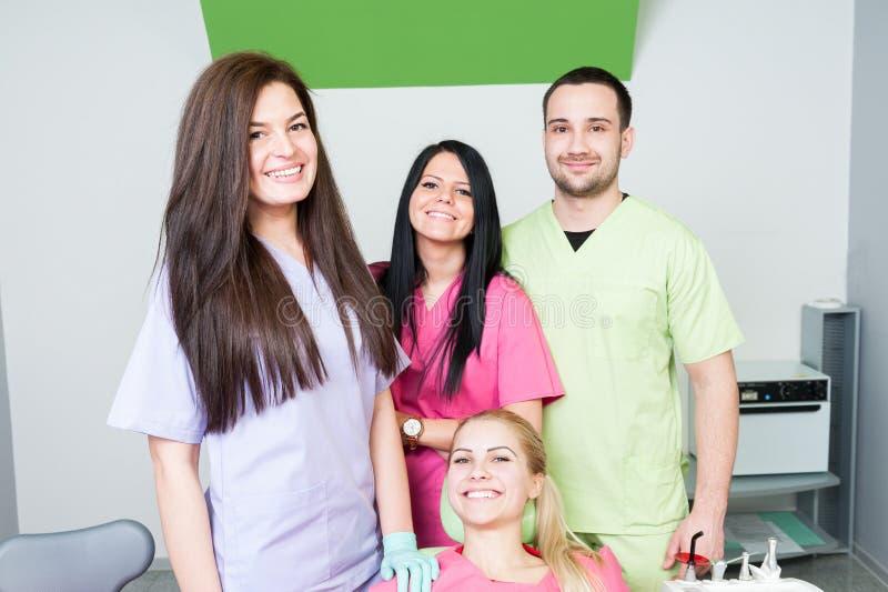 Equipe do dentista e paciente de sorriso fotografia de stock