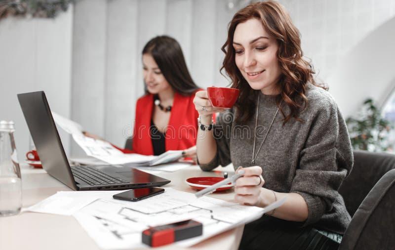 A equipe do desenhista de duas jovens mulheres est? trabalhando no projeto de design do assento interior na mesa com port?til e foto de stock royalty free