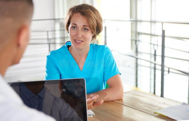 Equipe do doutor e da enfermeira que discutem um diagnóstico paciente que senta-se na mesa no escritório moderno brilhante imagens de stock