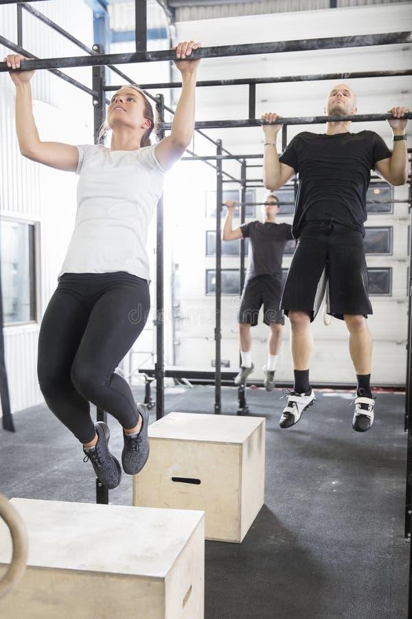 A equipe do exercício treina pullups no gym da aptidão imagens de stock