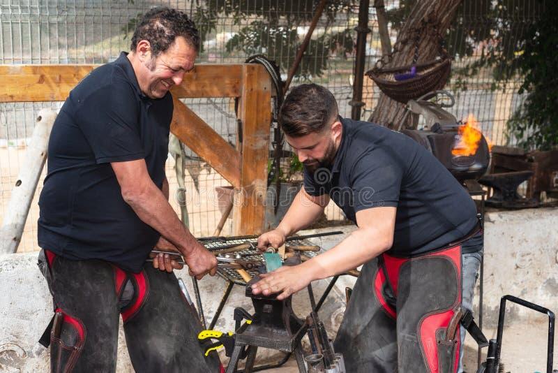 Equipe do ferreiro que trabalha no batente, fazendo uma ferradura imagem de stock royalty free