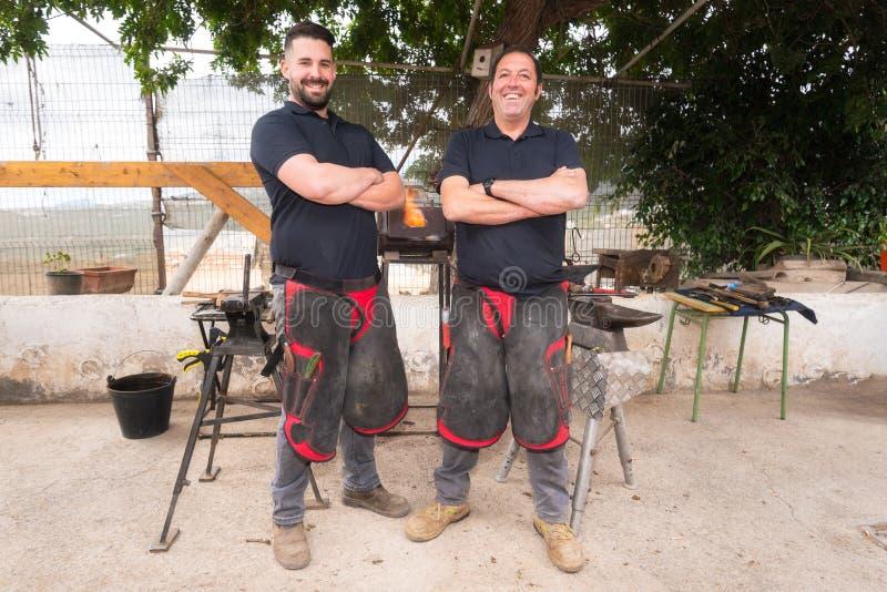 Equipe do ferreiro que trabalha no batente, fazendo uma ferradura fotografia de stock