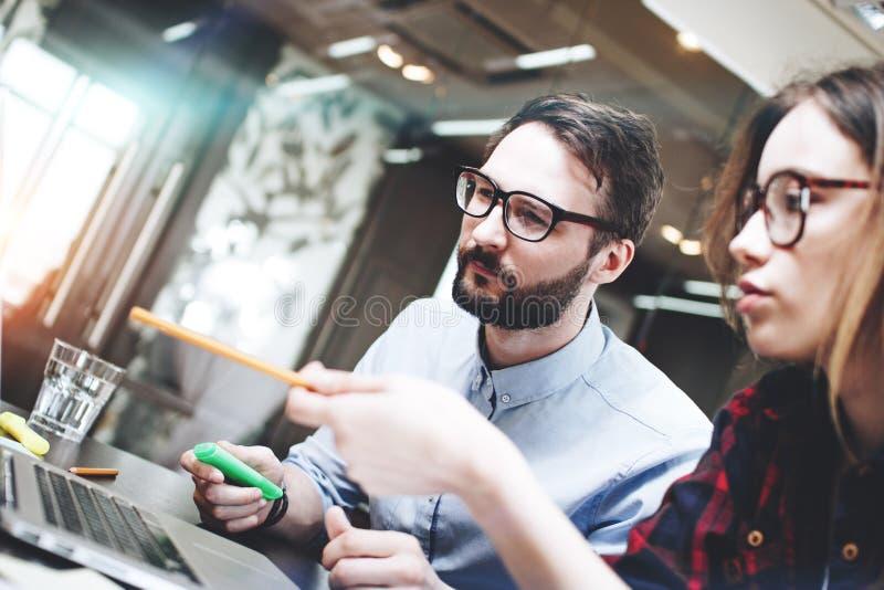 Equipe do homem de negócios que trabalha em um novo conceito atrás de um portátil moderno no escritório do espaço aberto Fundo bo imagens de stock