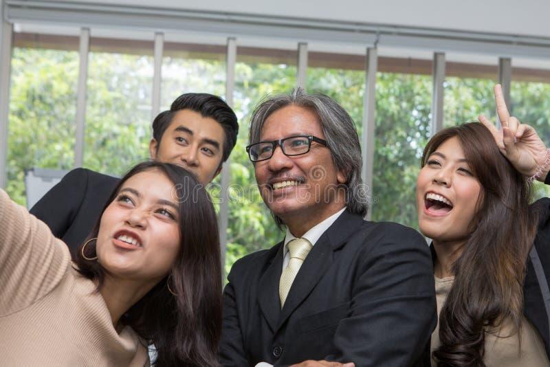 Equipe do negócio asiático que levanta na sala de reunião selfie da mulher na sala de reunião no escritório imagem de stock royalty free