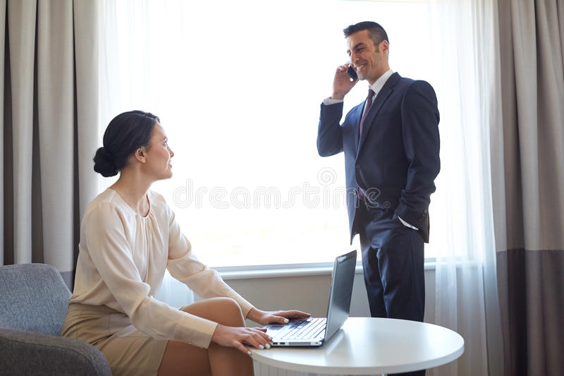 Equipe do negócio com o portátil que trabalha na sala de hotel foto de stock royalty free