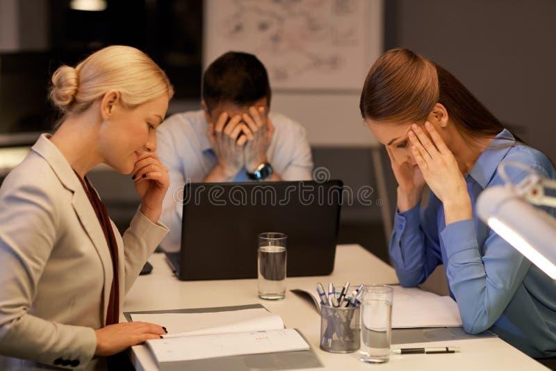 Equipe do negócio com o portátil que trabalha tarde no escritório imagens de stock royalty free