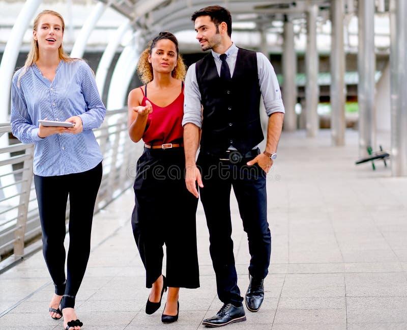 A equipe do negócio com um homem e duas mulheres estão andando e igualmente discutem sobre seu trabalho durante o tempo do dia na imagens de stock royalty free