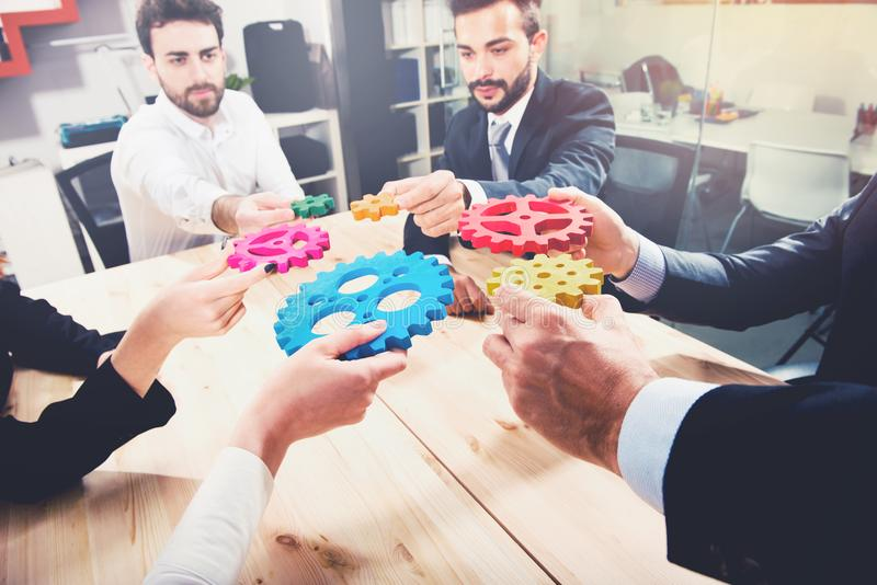 A equipe do negócio conecta partes de engrenagens Trabalhos de equipa, parceria e conceito da integração fotografia de stock royalty free