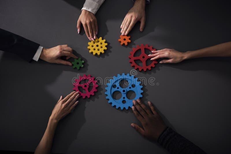 A equipe do negócio conecta partes de engrenagens Trabalhos de equipa, parceria e conceito da integração foto de stock