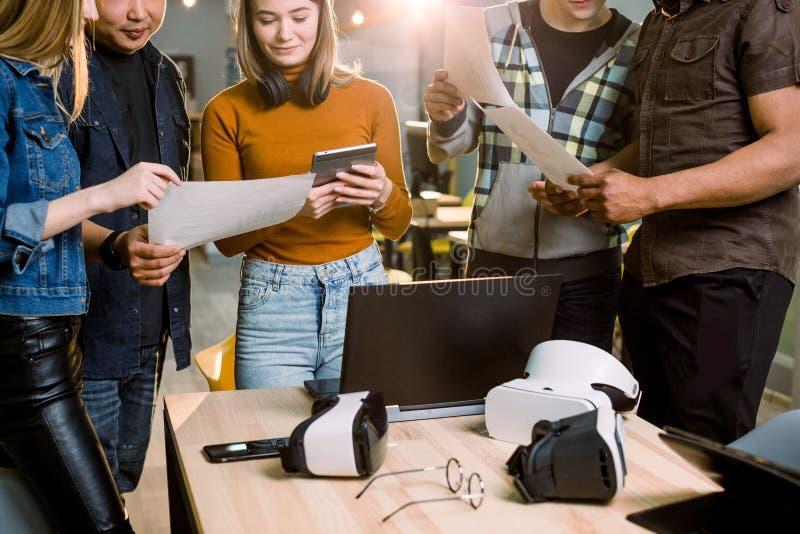 Equipe do negócio de cinco pessoas que trabalham junto com dispositivos e papéis Vidros ou óculos de proteção da realidade virtua imagens de stock
