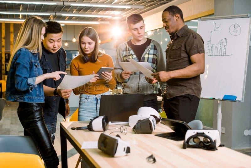 Equipe do negócio de cinco pessoas que trabalham junto com dispositivos e papéis Vidros ou óculos de proteção da realidade virtua fotografia de stock royalty free