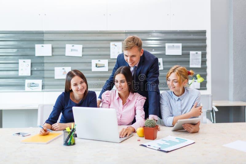 Equipe do negócio em um interior brilhante moderno do escritório no trabalho em um portátil foto de stock royalty free