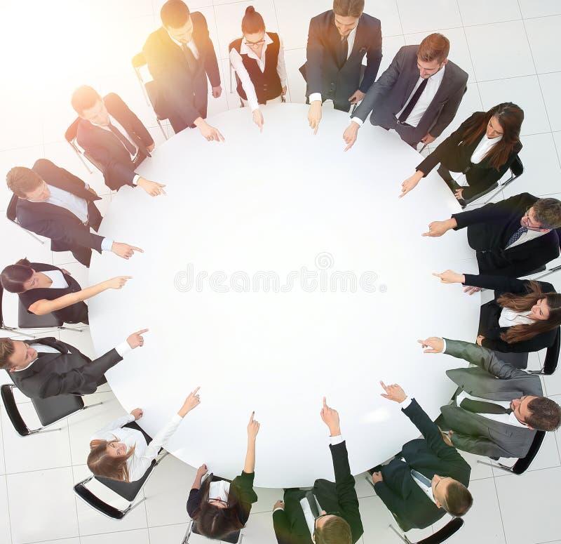 A equipe do negócio indica o centro da mesa redonda imagens de stock royalty free