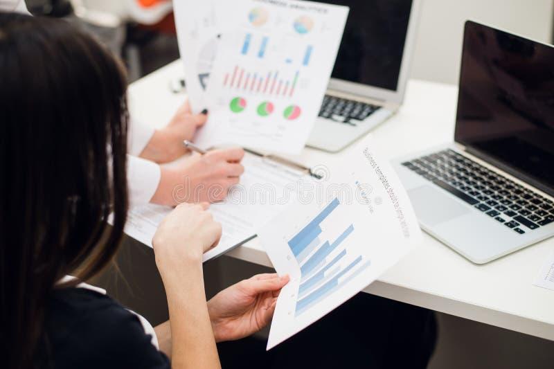 Equipe do negócio que analisa gráficos da renda com laptop modernos Feche acima do conceito da análise e da estratégia fotografia de stock