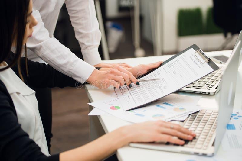 Equipe do negócio que analisa gráficos da renda com laptop modernos Feche acima do conceito da análise e da estratégia imagem de stock