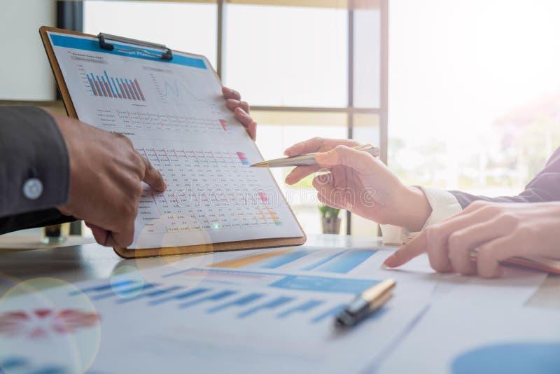 Equipe do negócio que analisa o plano e a estatística do orçamento imagem de stock
