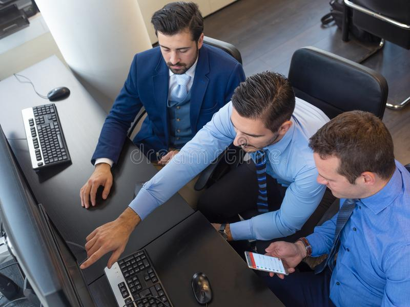 Equipe do negócio que analisa os dados de comércio no computador no escritório de troca incorporado foto de stock royalty free