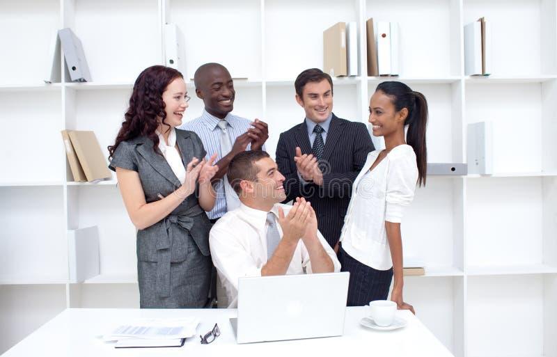 Equipe do negócio que aplaude um colega foto de stock