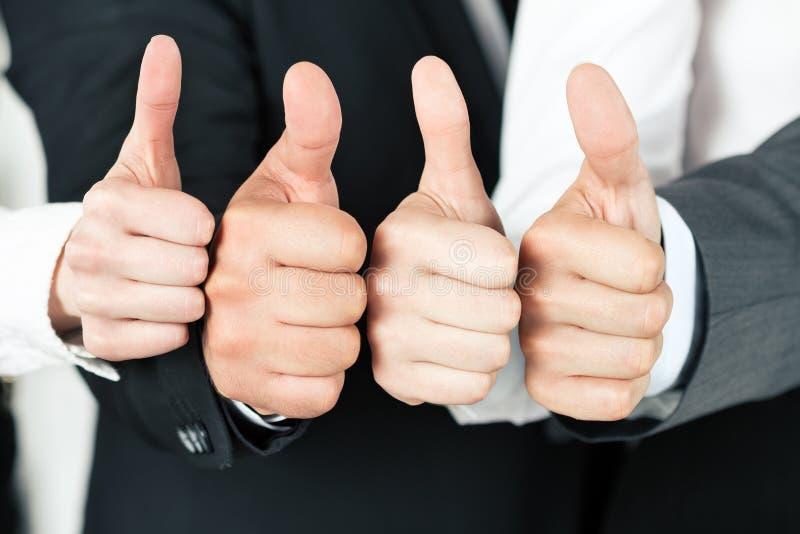 Equipe do negócio que aponta acima de seus polegares fotografia de stock