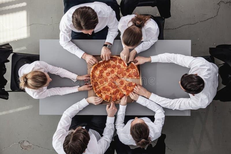 Equipe do negócio que come a pizza foto de stock