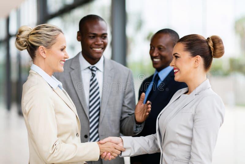 Equipe do negócio que dá boas-vindas à mulher de negócios imagens de stock