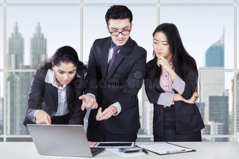 Equipe do negócio que discute com o portátil imagens de stock royalty free