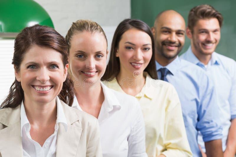 Equipe do negócio que está em seguido de sorriso na câmera foto de stock