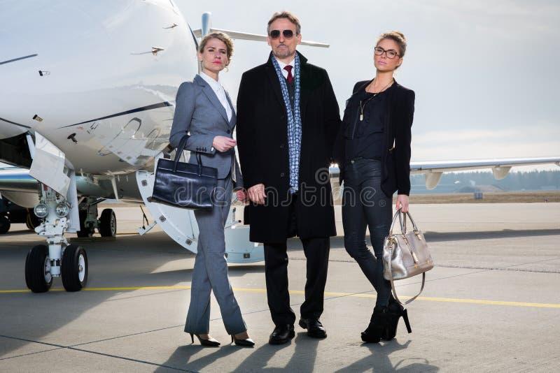 Equipe do negócio que está na frente do jato privado fotografia de stock