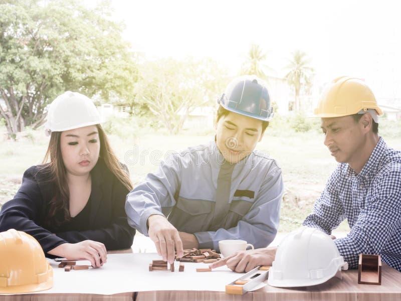 Equipe do negócio que faz uma estrutura com cubos de madeira Construindo um conceito do neg?cio imagens de stock royalty free