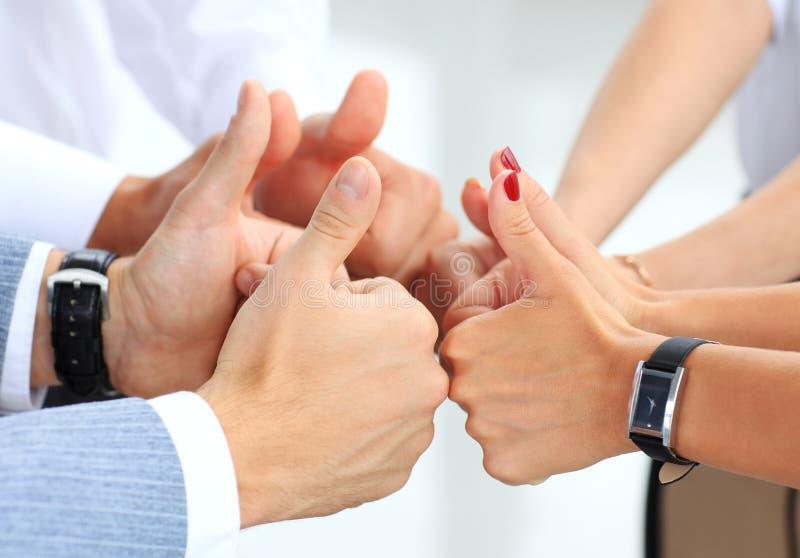 Equipe do negócio que mantém seus polegares fotografia de stock royalty free