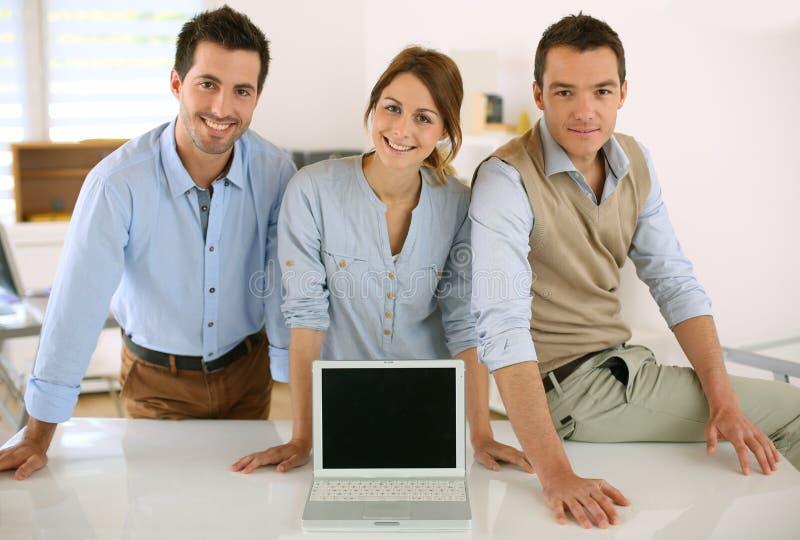Equipe do negócio que mostra o texto ou os resultados na tela do portátil foto de stock