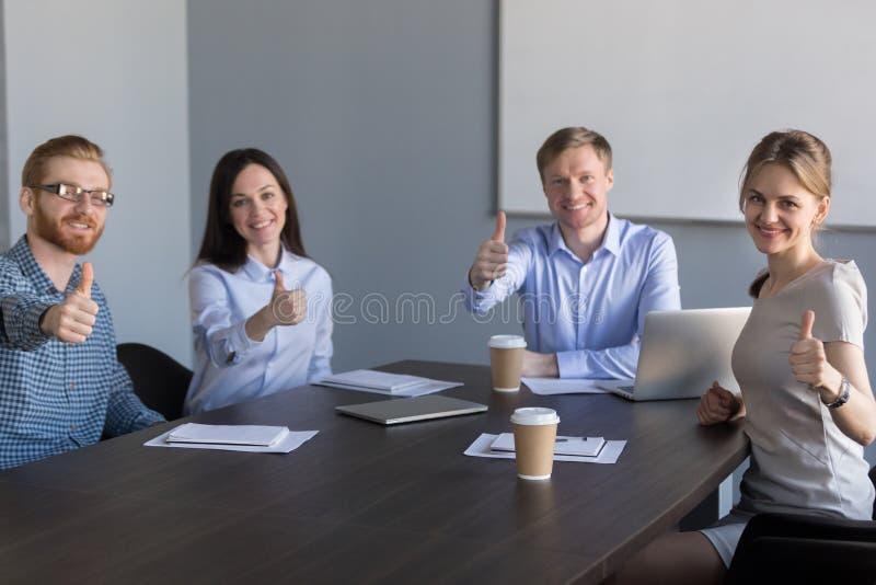 Equipe do negócio que olha a câmera que mostra os polegares acima na reunião imagens de stock royalty free
