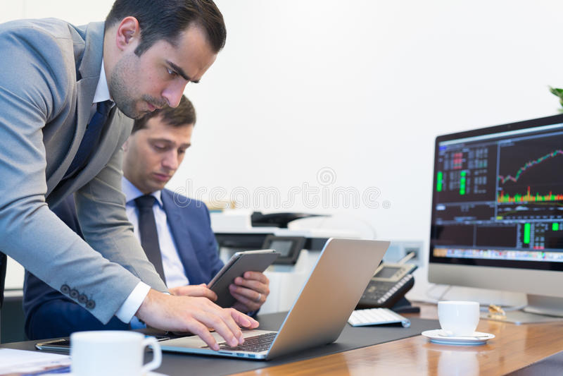 Equipe do negócio que resolve remotamente um problema na reunião de negócios que usa o laptop e o touchpad fotos de stock