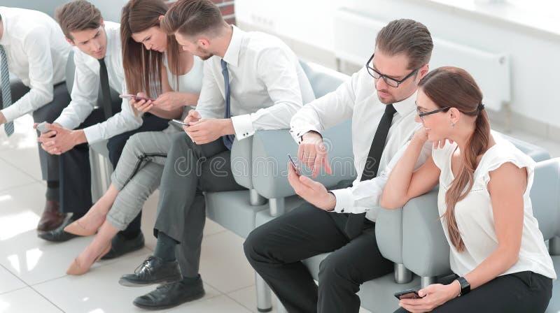 Equipe do negócio que senta-se na entrada do cente do negócio imagem de stock royalty free