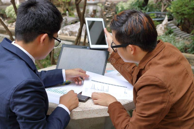 Equipe do negócio que senta-se no mármore no parque e que trabalha com portátil, tabuleta e cartas foto de stock