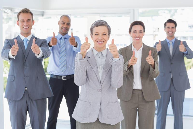Equipe do negócio que sorri na câmera que mostra os polegares acima imagem de stock