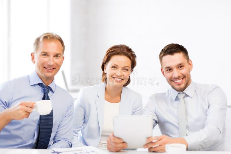 Equipe do negócio que tem o divertimento com o PC da tabuleta no escritório imagem de stock