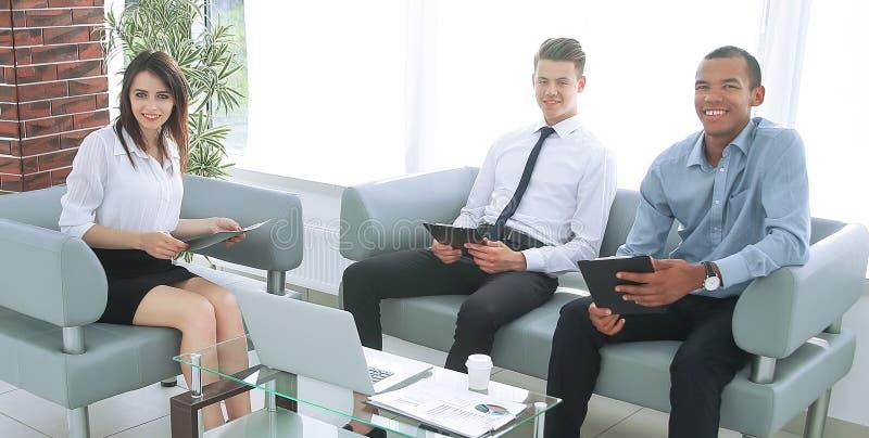 Equipe do negócio que trabalha com os documentos, sentando-se no escritório foto de stock royalty free