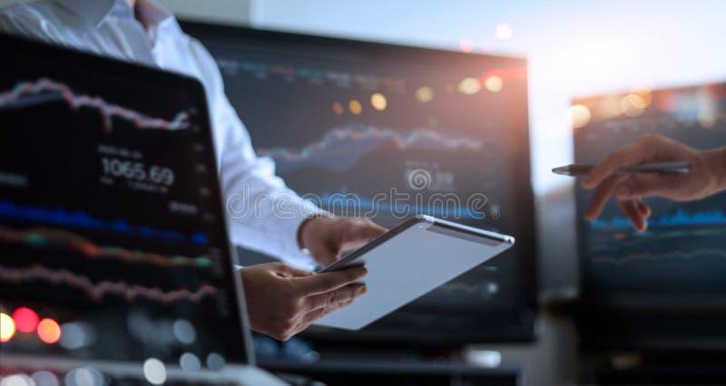 Equipe do negócio que trabalha junto, usando a tabuleta para analisar o mercado de valores de ação dos dados em monitorar a sala  imagens de stock