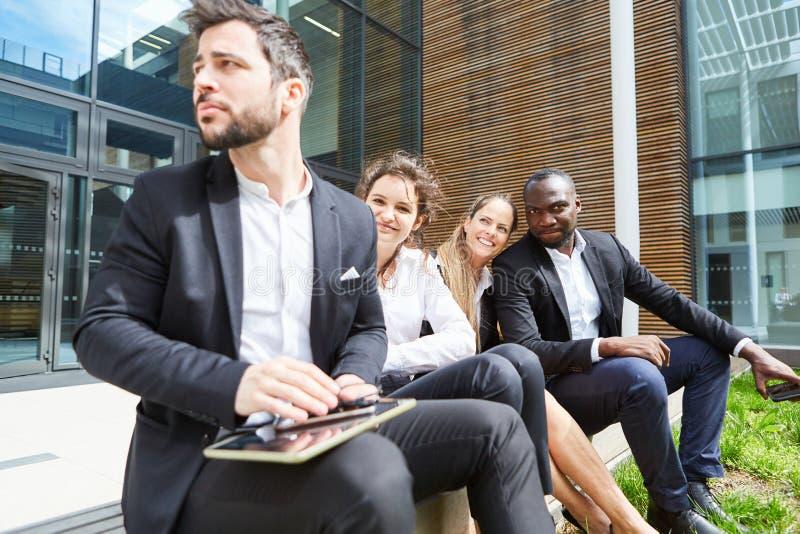 A equipe do negócio toma uma ruptura na frente do escritório imagens de stock royalty free